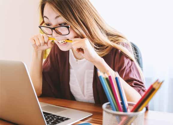 Un fille mange son crayon devant l'écran de son ordinateur, apparemment elle ne trouve pas la solution